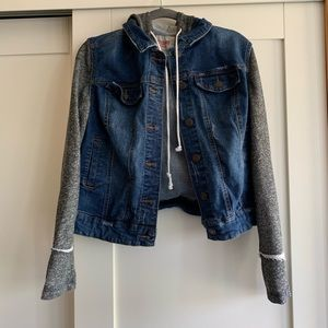 Jean jacket with grey cloth sleeves.